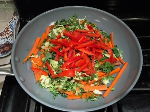 Carrot, Red Pepper, & Brussel Sprout slices in pan for Asian Lettuce Wraps. They are a fantastic way to use leftover Turkey or Chicken transforming it with new delicious flavors and textures. The turkey is stir fried with carrots, red pepper, and brussel sprouts in a flavorful ginger, garlic, & sesame sauce. It's layered in lettuce wraps with rice and a cool, crunchy purple cabbage sesame slaw. Serve with a Garlic Honey Soy Sauce....YUM!!!