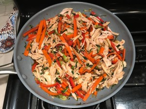 Shredded Turkey and stir fry veggies in pan for Asian Lettuce Wraps. They are a fantastic way to use leftover Turkey or Chicken transforming it with new delicious flavors and textures. The turkey is stir fried with carrots, red pepper, and brussel sprouts in a flavorful ginger, garlic, & sesame sauce. It's layered in lettuce wraps with rice and a cool, crunchy purple cabbage sesame slaw. Serve with a Garlic Honey Soy Sauce....YUM!!!