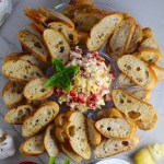 Bruschetta Topping surrounded by crostini on a platter with one crostini topped on a plate. It combines fresh tomatoes, artichoke hearts, garlic, basil, olive oil, and GOAT CHEESE!  Top on toasty garlic crostini and you get fresh bright flavors with both crunch and creamy in every bite.