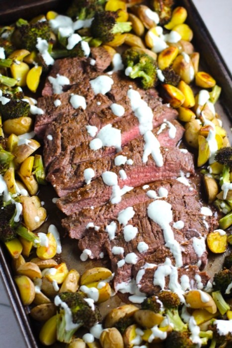 Flank Steak sliced with Potatoes & Broccoli on sheet pan with crema drizzled on top. This is an easy and delicious Sheet Pan Dinner.  The homemade steak rub adds such wonderful flavor. To top this sheet pan dinner, you get this tangy, light Garlic Chive Crema!  Best of all, you only need 1 pan so it's a super easy clean up.  Easy and Delicious!