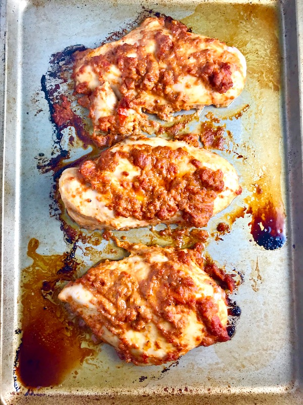 Sun Dried Tomato Chicken breasts cooked on a pan. It's slightly sweet, slightly tart and tangy, and hugely delicious! When Sun dried tomatoes are rehydrated and blended, they turn into a thick and lucious sauce that coats the chicken keeping it moist and juicy when it simply bakes in the oven. It's a perfect easy weeknight dinner that you can prepare ahead and cook quickly! #chicken #chickenrecipes #easydinners #dinnerrecipes