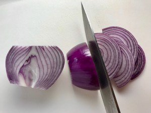 Red Onions being sliced for pickling for Slow Cooker Pork Tacos with with Pickled Onions, Shredded Cheese, and Cilantro Lime Crema drizzled on top!  It's such an easy dinner since the pork cooks in the slow cooker to be perfectly seasoned and fall apart tender. #tacos #easydinner #glutenfree #dinner #mexican #pork