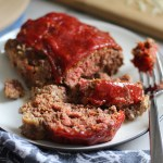 5-Ingredient Chipotle Meatloaf sliced on white plate. This recipe adds a spicy mexican flare with Chipotle Peppers in Adobo Sauce and Cheddar Cheese.  It's incredibly easy, incredibly moist, and incredibly delicious!  A family dinner favorite! #meatloaf #mexican #easydinner #familydinner #dinner #easyrecipes #beef
