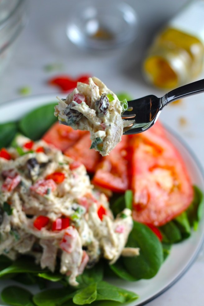 Fork with bite of Curry Chicken Salad on spinach with tomato slices. It has so many fantastic flavors and textures! The chicken breast is simply roasted and mixed with a creamy sweet and savory curry dressing. Red pepper gives you a fresh crunch, scallion gives a savory bite, and raisins give a burst of sweet. #chicken #chickenrecipes #chickensalad #currychicken #mealprep #lunch #healthyrecipes