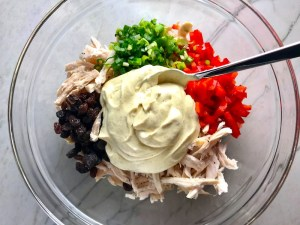Curry Dressing, shredded chicken, red pepper, scallion, and raisins in bowl for Curry Chicken Salad. It has so many fantastic flavors and textures!  The chicken breast is simply roasted and mixed with a creamy sweet and savory curry dressing.  Red pepper gives you a fresh crunch, scallion gives a savory bite, and raisins give a burst of sweet.  #chicken #chickenrecipes #chickensalad #currychicken #mealprep #lunch #healthyrecipes