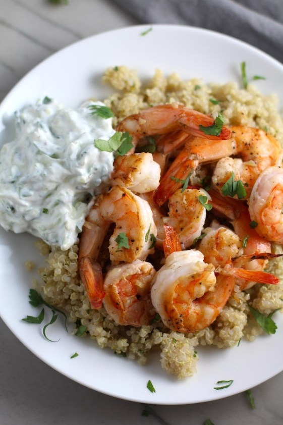 Garlic and Lime Shrimp with Tzatziki Sauce over Quinoa on plate. The Shrimp is simply sauteed with minced garlic, olive oil, and lime for big bold flavors. The Tzatziki Sauce is bright and cool with creamy yogurt with fresh cucumber, lime, garlic, and scallion. #shrimp #easydinner #dinner #seafoodrecipes #shrimprecipes