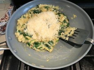 Adding parmesan to spinach and artichokes in pan for Spinach Artichoke Stuffed Zucchini. Each fantastic bite gives you creamy artichoke, nutty cheesy Parmesan, spinach, and zucchini. Prepare entirely ahead, then bake 20 minutes and enjoy! #vegetarian #zucchini #stuffedzuchini #spinach #artichoke #springrecipes #healthyfood #healthydinner #healthyrecipes #glutenfree