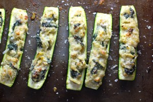 Spinach Artichoke Stuffed Zucchini on a pan. Each fantastic bite gives you creamy artichoke, nutty cheesy Parmesan, spinach, and zucchini. Prepare entirely ahead, then bake 20 minutes and enjoy! #vegetarian #zucchini #stuffedzuchini #spinach #artichoke #springrecipes #healthyfood #healthydinner #healthyrecipes #glutenfree