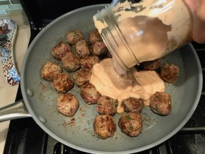 Adding Dill Cream Sauce to cooked meatballs in skillet for Meatballs in Cauliflower Dill Cream Sauce. #meatballs #swedishmeatballs #familydinner #easydinner #dinner #healthydinner