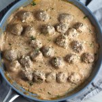 Meatballs in Cauliflower Dill Cream Sauce on plate with fork and skillet in background. The Meatballs are in a creamy cauliflower sauce with garlic, fresh dill, cream cheese, and tomato paste. #meatballs #swedishmeatballs #familydinner #easydinner #dinner #healthydinner