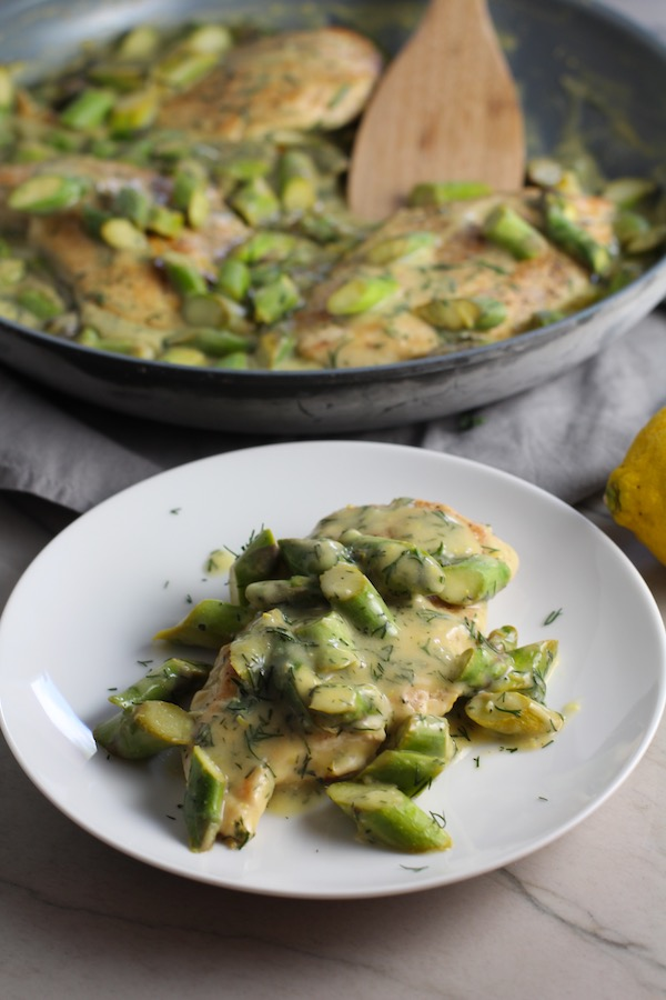Lemon Dill Sauce Chicken and Asparagus on plate with pan in back. It has chicken in a light and creamy sauce flavored with garlic, lemon and fresh dill. It's loaded with fresh asparagus. #springrecipes #dinner #easydinner #healthydinner #lemon #asparagus #chicken #glutenfree #easyrecipes