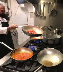 Cooking Class in Italy with chef flipping cherry tomatoes in pan.