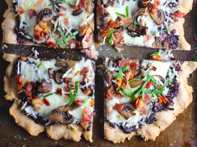 Flatbread cut into 4 pieces on a pan with a crispy gluten free crust, salty and briny Olive Tapenade, creamy mozzarella, earthy and meaty mushrooms, peppery pancetta, and fresh basil. #flatbread #pizza #olives #tapenade #mediterranean #easydinner #dinner