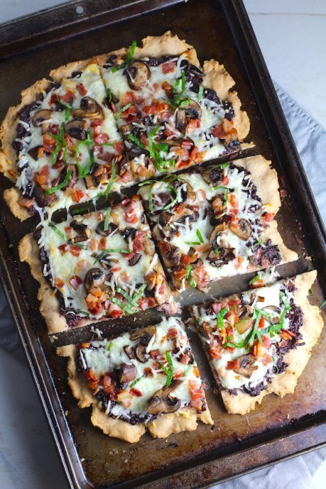 Flatbread cut into 6 pieces on a pan with a crispy gluten free crust, salty and briny Olive Tapenade, creamy mozzarella, earthy and meaty mushrooms, peppery pancetta, and fresh basil. #flatbread #pizza #olives #tapenade #mediterranean #easydinner #dinner