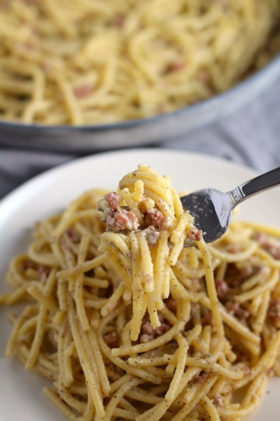 Pancetta, Parmesan, and Pepper Pasta on plate with fork holding bite. The Pancetta gives a salty and slightly peppery flavor, Parmesan cheese creates a nutty and creamy sauce, and the ground black pepper gives a peppery flavor that makes this pasta stand out. #pasta #easypasta #easydinner #dinner #italian #familydinner #onpotdinners #onepandinners #parmesan