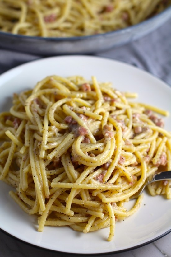 Pancetta, Parmesan, and Pepper Pasta on plate with fork and skillet in back. The Pancetta gives a salty and slightly peppery flavor, Parmesan cheese creates a nutty and creamy sauce, and the ground black pepper gives a peppery flavor that makes this pasta stand out. #pasta #easypasta #easydinner #dinner #italian #familydinner #onpotdinners #onepandinners #parmesan