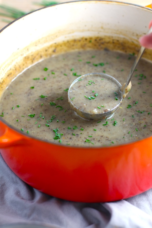 Thick & Creamy Mushroom Soup in a pot with ladle filled with earthy mushrooms, aeromatic onions, flavorful oregano, and bright chives.