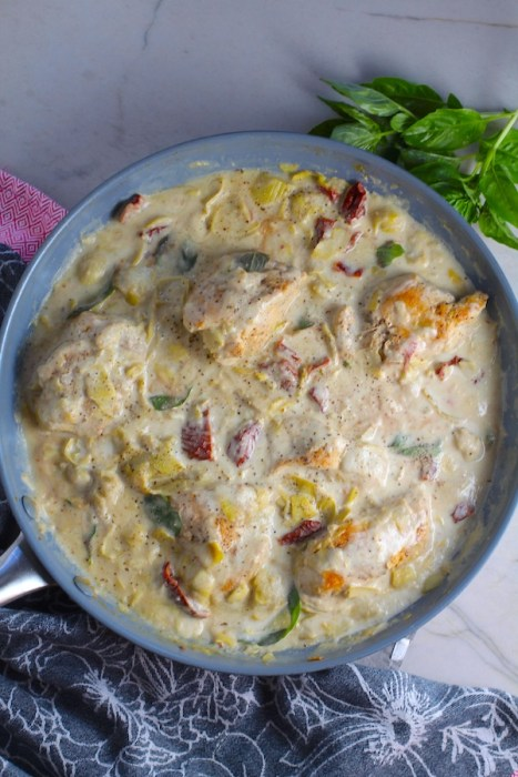 Close up of Skillet Artichoke Chicken with sun dried tomatoes, basil, garlic, in cream sauce. #skilletchicken #skilletdinner #chicken #easydinner #familydinner #italian #tuscanchicken