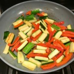 Red Peppers and Zucchini in pan for Family Coconut Curry. The sauce has onion, coconut milk, ginger, garlic, and warm Indian Curry spices.