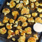 Baked Coconut Cauliflower Bites on pan. They have a slightly sweet and salty crunch outside from the shredded coconut and panko mixture. The inside is soft and creamy.