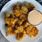Baked Coconut Cauliflower Bites on plate with Sriracha Mayo dipping sauce.  They have a slightly sweet and salty crunch outside from the shredded coconut and panko mixture.  The inside is soft and creamy.  Dip in the Sriracha Mayo.