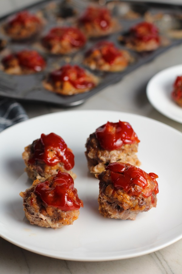 Mini Meatloaf Muffins on a plate. They have only 5 simple ingredients, cook in 30 minutes, and are gluten free. Parmesan gives salty and nutty flavor.  Ketchup on top cooks down into a thick, deep-flavored tangy, salty, and sweet glaze.