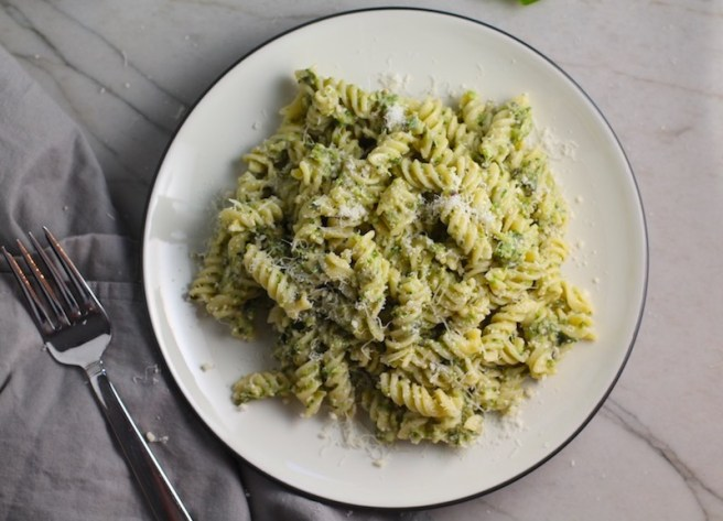 Broccoli Pesto Pasta on a plate with parmesan on top. It's delicious AND good for you! It has all of the classic pesto flavors from garlic, basil, parmesan cheese, and pine nuts. But the flavor is a bit more mellow by adding broccoli! #broccolirecipes #pesto #pasta #easydinner #dinnerideas #familydinner