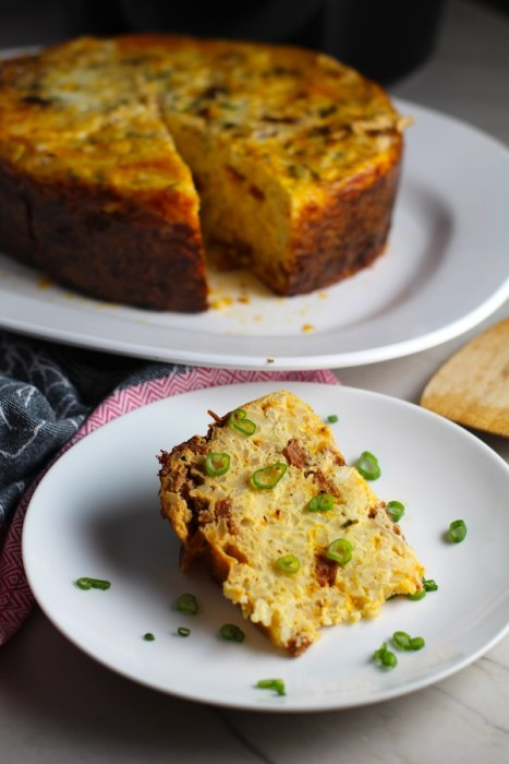 Piece of Slow Cooker Egg Casserole on a plate with scallions. It has Chorizo, Potatoes and both cheddar and manchego cheeses. IT COOKS WHILE YOU SLEEP! #eggs #eggcasseroles #eggrecipes #breakfastideas #holidayrecipes