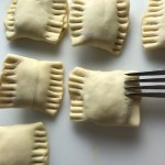 Fork sealing uncooked Mini Beef Wellington Bites. They are flaky and buttery Puff Pastry is filled with a creamy mushroom and parmesan filling and tender beef filet.  #appetizers #partyfood