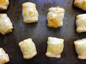 Cooked Mini Beef Wellington Bites on pan. They are flaky and buttery Puff Pastry is filled with a creamy mushroom and parmesan filling and tender beef filet.  #appetizers #partyfood