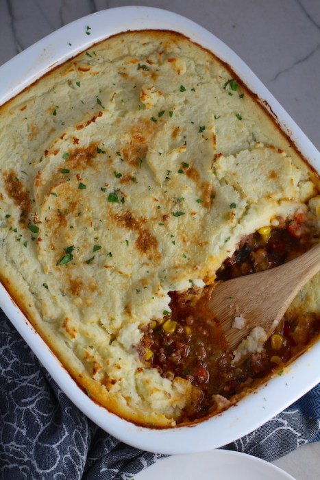 Spatula in Cottage Pie in casserole dish. This recipe has Spanish Chorizo and ground beef cooked in a rich and savory gravy with veggies and herbs.  Creamy mashed potatoes sit on top with manchego, parmesan, and garlic. #dinnerideas #cottagepie #shepherdspie