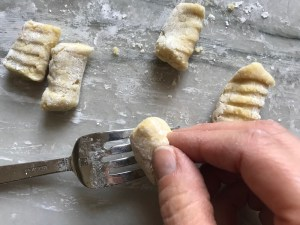 Rolling gnocchi on fork on for cauliflower gnocchi.  These Gnocchi are soft, silky, buttery, and melt-in-your-mouth! Made with cauliflower, they're a healthier version to traditional gnocchi! Add my simple Garlic Butter Sauce or Tomato Sauce and they are heaven. #dinnerideas #gnocchi #cauliflower