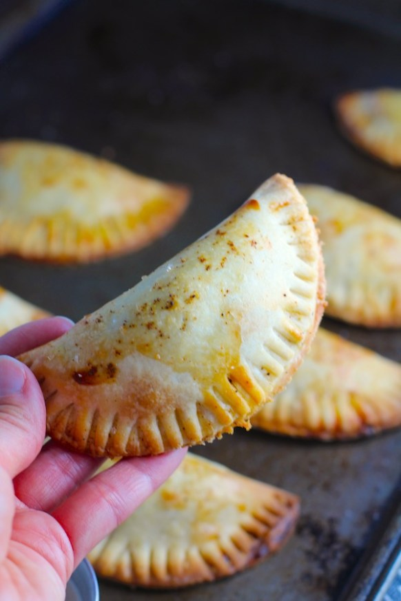 Hand holding a Ground Beef Empanada with more on a pan. Flaky, buttery pastry on the outside with a savory, smokey, salty ground beef filling.