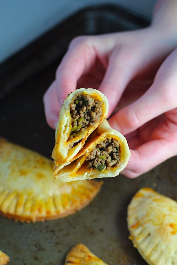 Hands holding a Ground Beef Empanada with more on a pan. Flaky, buttery pastry on the outside with a savory, smokey, salty ground beef filling.