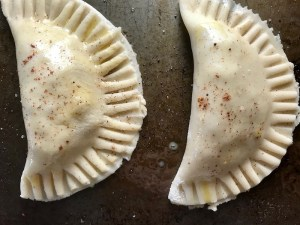 Raw Ground Beef Empanadas on a pan. Flaky, buttery pastry on the outside with a savory, smokey, salty ground beef filling.