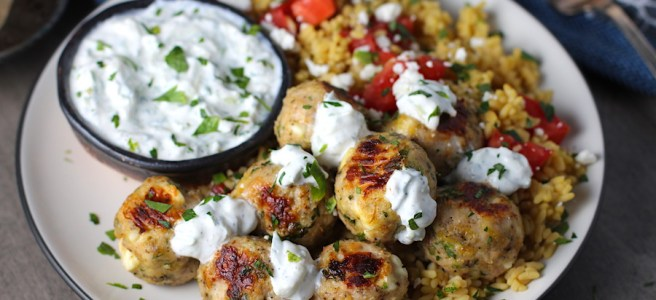 Ground Chicken Greek Meatballs on a plate with Tzatziki sauce over rice. Baked meatballs in back. These meatballs have garlic, feta, parsley, and oregano.