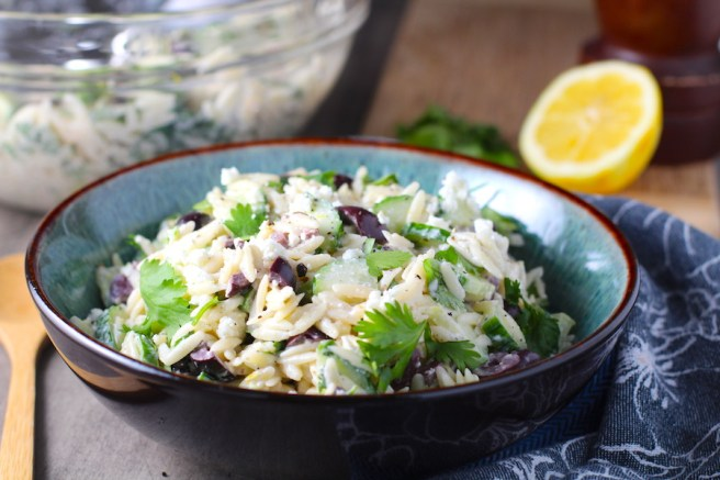 Greek Orzo Salad with Kalamata Olives, Cucumbers, and Feta Cheese in a bowl with lemon on side. It's mixed with a creamy lemon dressing that's bright and light!