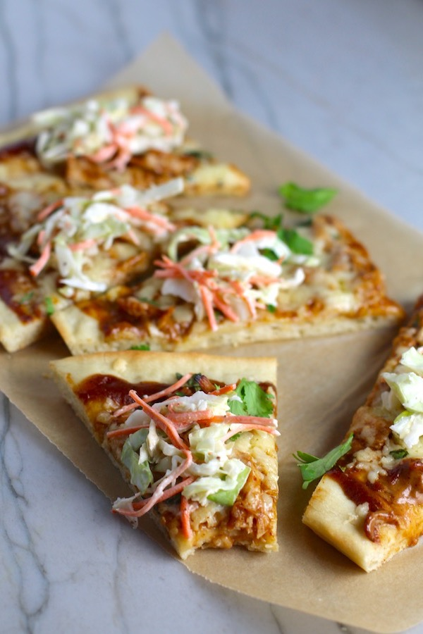 Sliced BBQ Chicken Pizza recipe with coleslaw and cilantro on top. It has homemade pizza crust, tangy and creamy BBQ sauce, hearty shredded chicken, cheddar cheese and coleslaw on top!