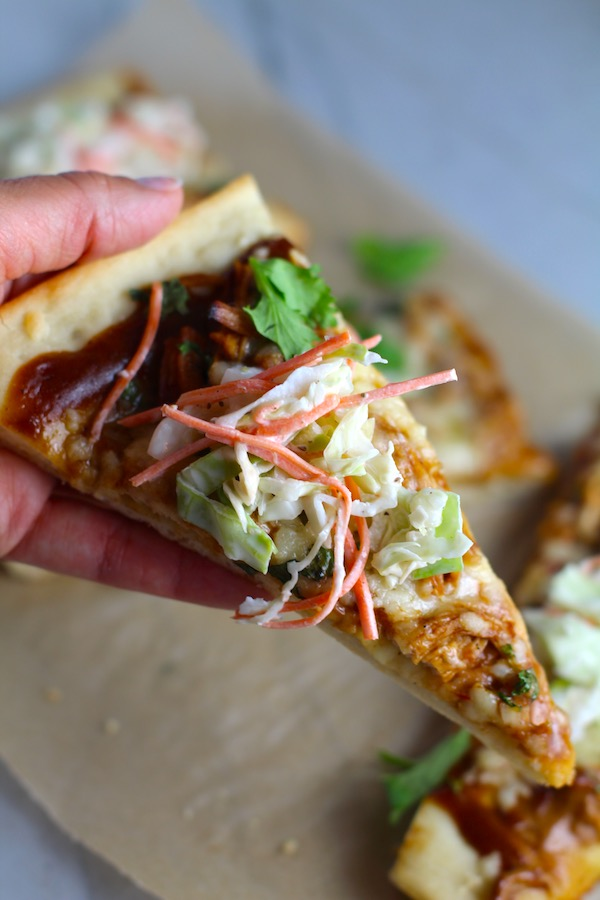 Hand holding slice of BBQ Chicken Pizza recipe with coleslaw cilantro on top. It has homemade pizza crust, tangy and creamy BBQ sauce, hearty shredded chicken, cheddar cheese and coleslaw on top!