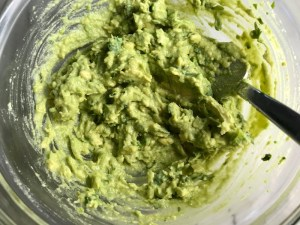 Mixed Guacamole for a Taco Chicken Burger recipe. The burger has smokey taco seasonings, cilantro, and scallions. Then on top are melty cheese, guacamole, lettuce, tomato, and chipotle mayonnaise!