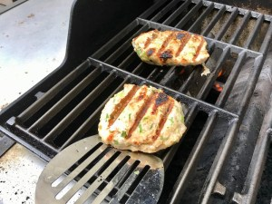 Grilled chicken burger on gas grill for a Taco Chicken Burger recipe. The burger has smokey taco seasonings, cilantro, and scallions. Then on top are melty cheese, guacamole, lettuce, tomato, and chipotle mayonnaise!