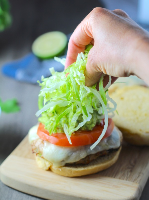 Hand putting lettuce on a Taco Chicken Burger with smokey taco seasonings, cilantro, and scallions, cheese, guacamole, tomato, and chipotle mayonnaise!
