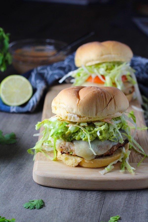 Two Taco Chicken Burgers on wood platter with smokey taco seasonings, cilantro, and scallions.  Then on top are melty cheese, guacamole, lettuce, tomato, and chipotle mayonnaise!