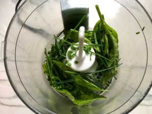 Basil and chives in food processor for Green Rice Recipe. It takes white rice from plain to amazing with just 5 ingredients. Filled with herbs and spinach, it has the perfect herby flavor.