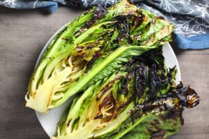 Grilled romaine lettuce halves for Flank Steak Salad Recipe with halved grape tomatoes, and creamy basil yogurt dressing.