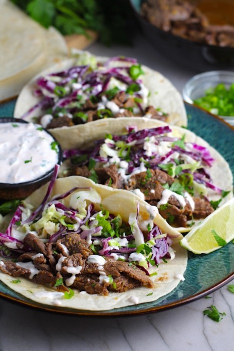 Korean Beef Tacos on a plate with flavorful Korean beef, crunchy Sesame Cabbage Slaw and a creamy, cool, Cilantro Lime Sriracha sauce!