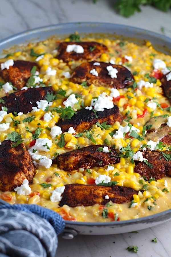 Creamy Corn and Blackened Chicken with feta and cilantro on top in a pan.