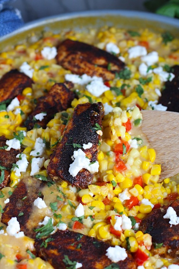 Creamy Corn and Blackened Chicken with feta and cilantro on top in a pan with spatula scooping.