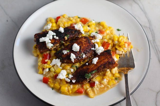 Creamy Corn and Blackened Chicken with feta and cilantro on top on a plate with fork.