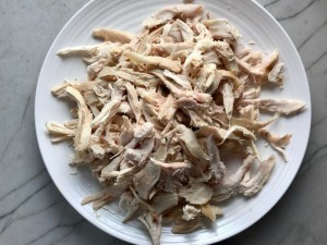 Shredded chicken on plate for Chicken Mole Enchiladas.